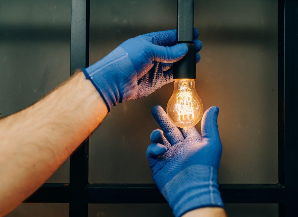 Electrician changes the light bulb, handyman