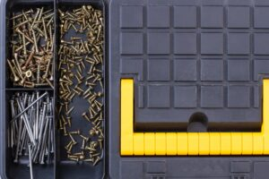 Screws and nails in plastic box close up.